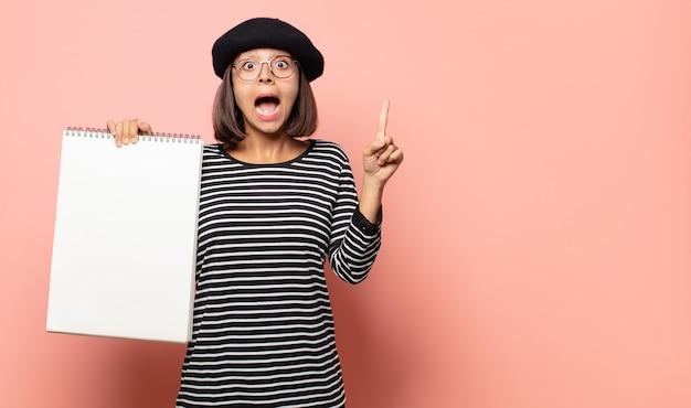 Giovane artista donna che si sente come un genio felice ed eccitato dopo aver realizzato un'idea, alzando allegramente il dito, eureka!