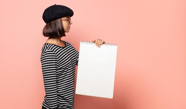 Artista della giovane donna sulla vista di profilo che cerca di copiare lo spazio davanti, pensare, immaginare o sognare ad occhi aperti