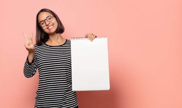 Artista della giovane donna che sorride e che sembra felice, spensierato e positivo, gesticolando vittoria o pace con una mano