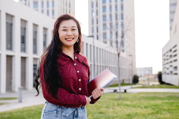 Studente asiatico della giovane donna allo spazio della copia del campus universitario