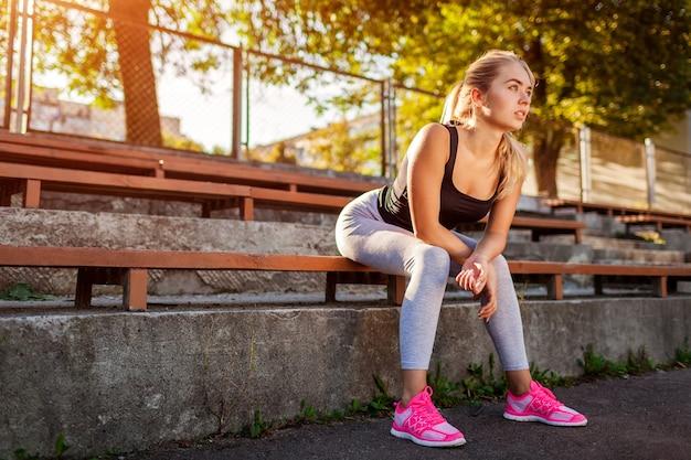 Atleta della giovane donna che ha resto dopo l'esecuzione sul campo sportivo in estate. donna sportiva che si siede sulla panchina dopo l'allenamento