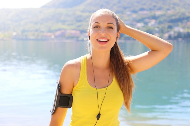 Giovane donna atleta che indossa canotta e fascia da braccio telefono guardando la fotocamera