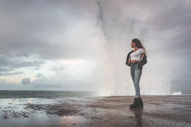 Giovane donna che assiste a come le onde colpiscono le rocce.