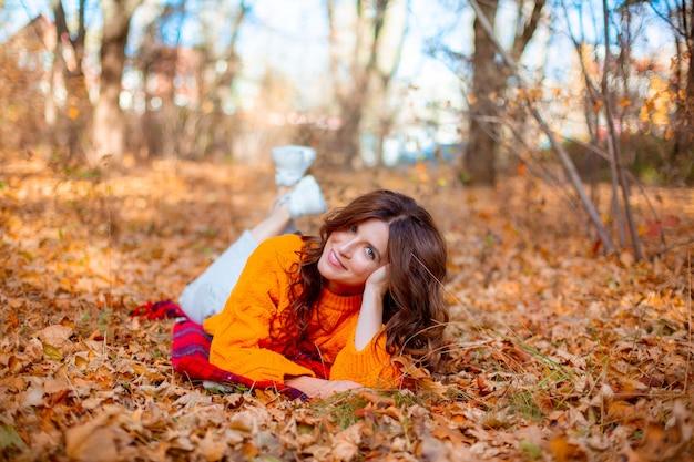 Una giovane donna in un parco autunnale con un maglione arancione