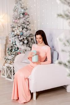 Giovane donna sullo sfondo dell'albero di natale con un regalo di capodanno nelle sue mani.