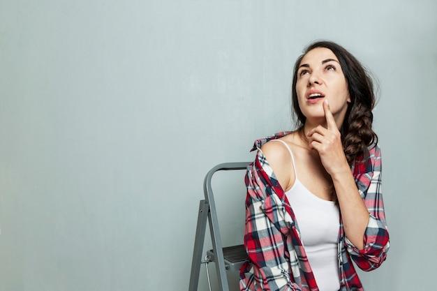 Una giovane donna sullo sfondo di un muro dipinto siede su una scala a pioli. bella bruna con una treccia. costruzione e riparazione. spazio per il testo.