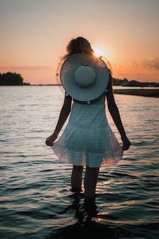 Giovane donna sullo sfondo della foto vista posteriore del tramonto di una bella bionda in abito bianco e...