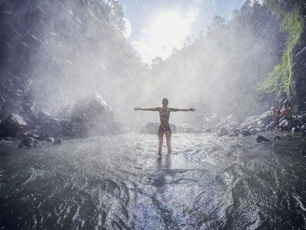 Viaggiatore con zaino e sacco a pelo della giovane donna che guarda cascata in giungle. ragazza di viaggio di immagine di concetto di ecoturismo