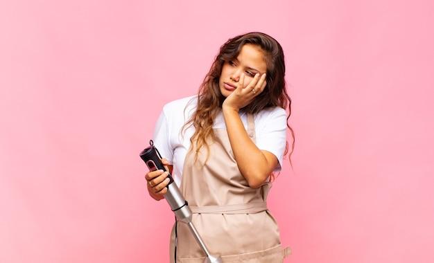 Panettiere di giovane donna che si sente annoiato, frustrato e assonnato dopo un compito noioso, noioso e noioso, tenendo la faccia con la mano