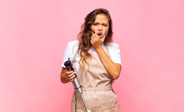 Panettiere di giovane donna con la bocca e gli occhi ben aperti e la mano sul mento, sentendosi spiacevolmente scioccati, dicendo cosa o wow