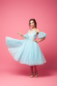 Una giovane donna in abito da ballo si erge su uno sfondo rosa una bella bruna in un lussureggiante abito blu con...