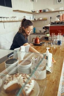 Barista di giovane donna con in piedi e pulizia del bancone del bar in una caffetteria, bancone disinfettante.