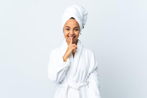 Giovane donna in accappatoio su sfondo bianco isolato che mostra un segno di silenzio gesto mettendo il dito in bocca