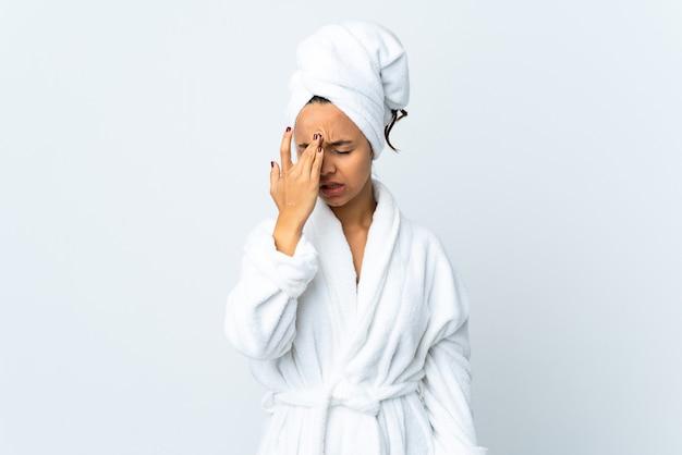 Giovane donna in accappatoio su sfondo bianco isolato con mal di testa
