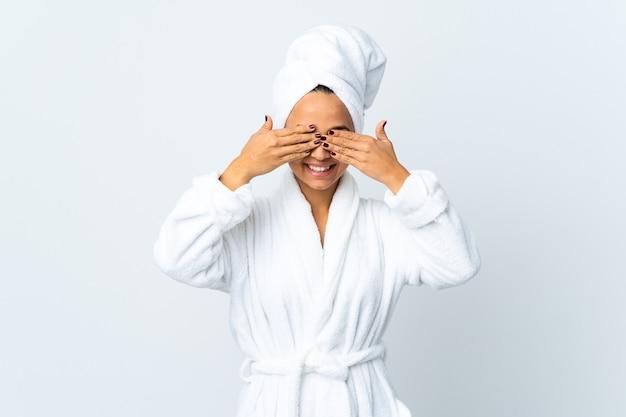 Giovane donna in accappatoio sopra la parete bianca isolata che copre gli occhi con le mani e sorridente