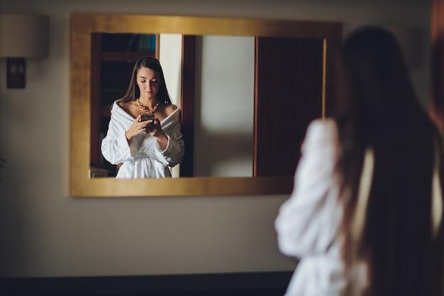 Giovane donna in accappatoio con smartphone alla spa