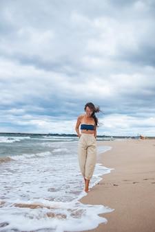 Giovane donna sulla spiaggia in una giornata nuvolosa