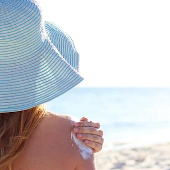 La giovane donna sulla spiaggia usa la protezione solare. foto di alta qualità