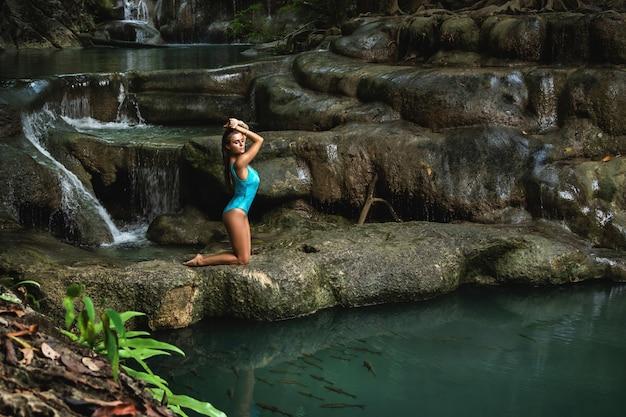 Giovane e donna sulla bellissima cascata nella giungla