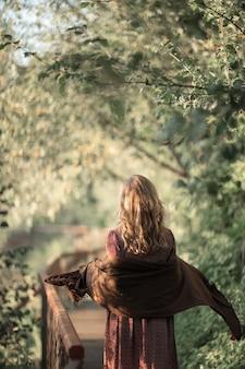 La giovane donna in vestito bello di liquidazione cammina nel parco forestale di giorno pieno di sole di estate la ragazza si rilassa la libertà in aria fresca primo piano vista posteriore verticale spazio della copia movimento foresta beckground