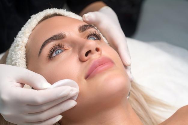 Giovane donna in un salone di bellezza. l'estetista esegue una procedura di pulizia del viso.