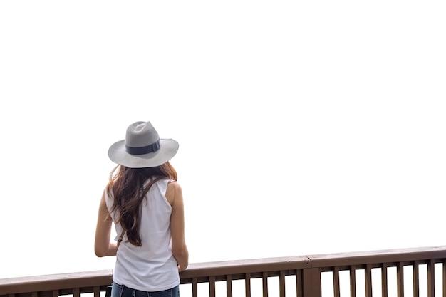 Abbronzatura di bellezza della giovane donna con il cappello che sta sul terrazzo di legno