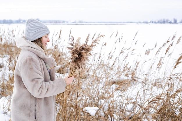 Una giovane donna in un abito beige di colori neutri raccoglie l'erba della pampa