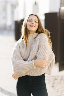 Una giovane donna in un maglione lavorato a maglia beige cammina per la città e sorride magnificamente
