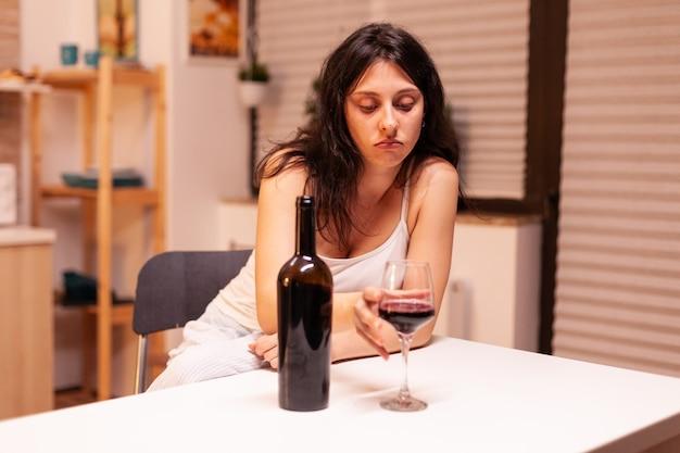 Giovane donna ubriaca con in mano un bicchiere di vino rosso seduto al tavolo della cucina. malattia della persona infelice e ansia che si sente esausta per avere problemi di alcolismo.