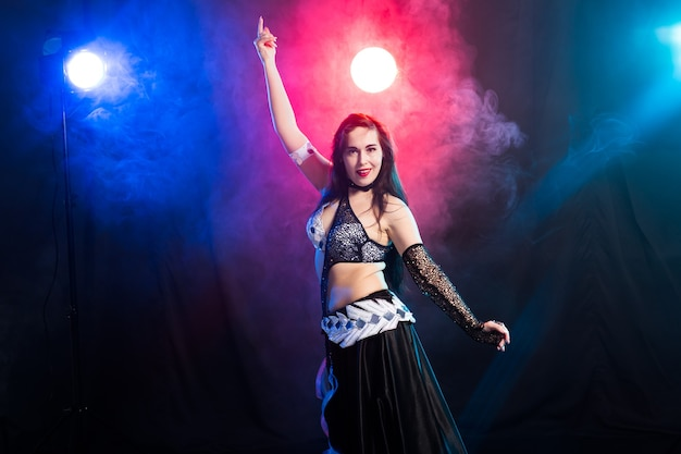 Giovane donna danzatrice del ventre in abito esotico con oro, danza danza tribale fusion in studio.
