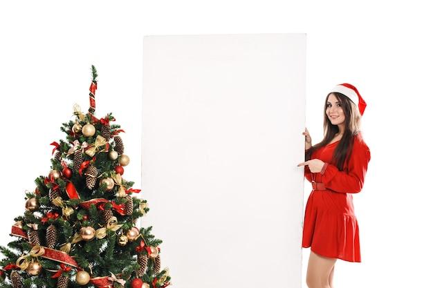 Giovane donna accanto all'albero di natale con un foglio di carta bianco