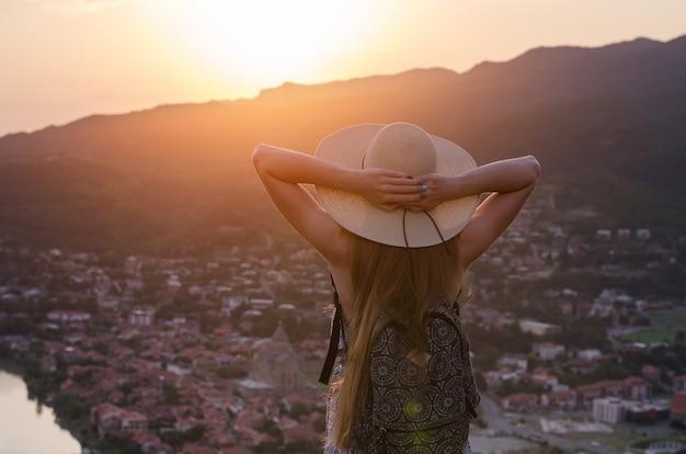 Giovane donna con grande cappello guardando il tramonto sulla città e mettere le mani sulla testa