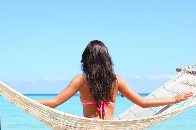 Giovane donna in bikini che oscilla in hummock sulla spiaggia tropicale