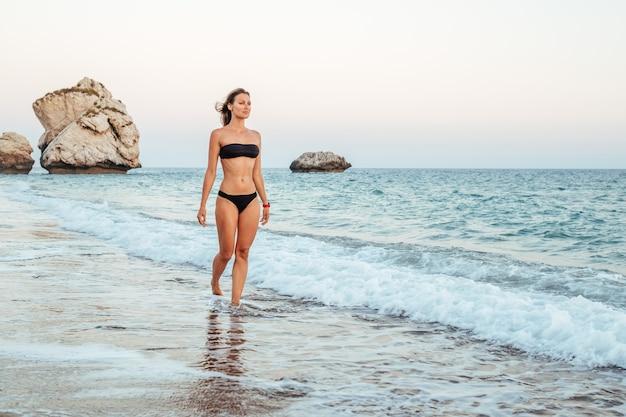 Giovane donna in bikini nero sulla spiaggia