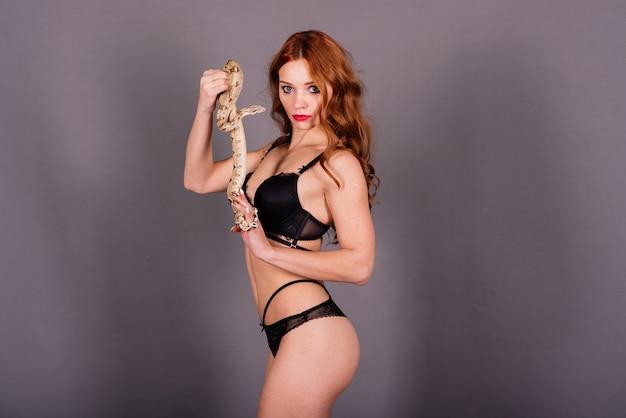 Giovane donna in bikini nero in posa con pitone su sfondo astratto