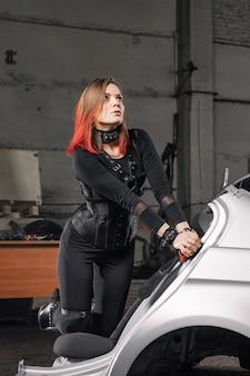 Giovane donna in un corsetto nero e con imbracature in pelle su sfondo di officina.