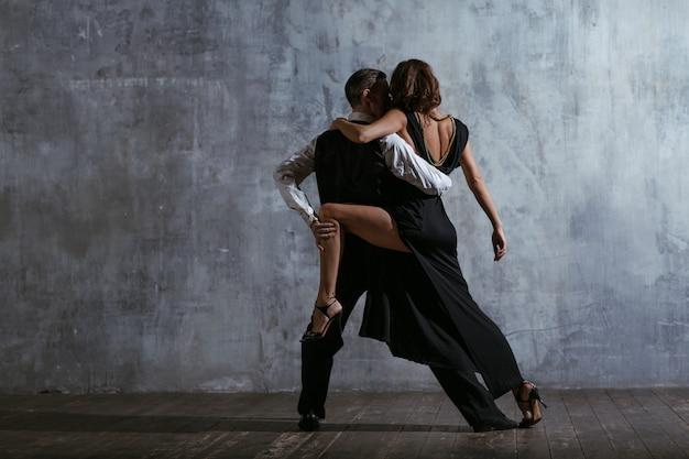 Giovane donna in abito nero e uomo danza tango