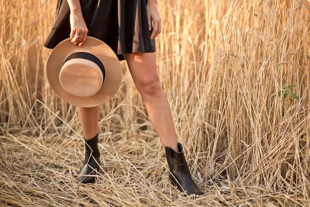 Giovane donna in abito nero in piedi nel campo di grano