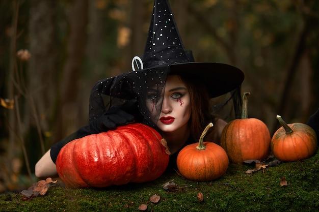 Giovane donna in abito nero con cappello da strega e zucca arancione disposta intorno nella foresta, concetto di halloween