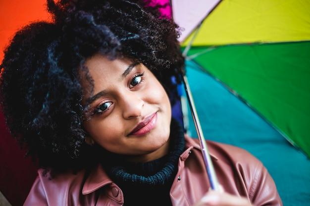 Giovane donna di etnia nera con la bandiera colorata arcobaleno. bellissimo ritratto della ragazza.