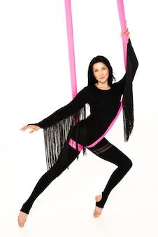 Giovane donna in tuta nera pratica yoga antigravità inversione aerea con amaca rosa