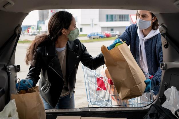 Giovane donna in giacca di pelle nera, maschera protettiva e guanti che assumono sacchi di carta