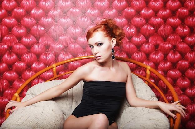 Giovane donna in lingerie nera seduta su una sedia