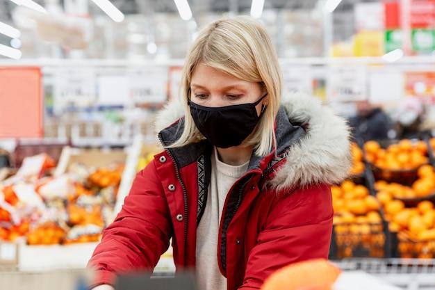 Giovane donna in una mascherina medica nera nel supermercato nel reparto con frutta e verdura.