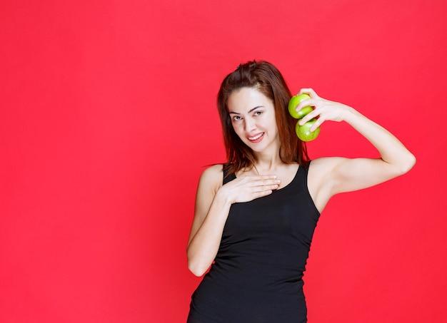 Giovane donna in canottiera nera che tiene mele verdi e indica se stessa