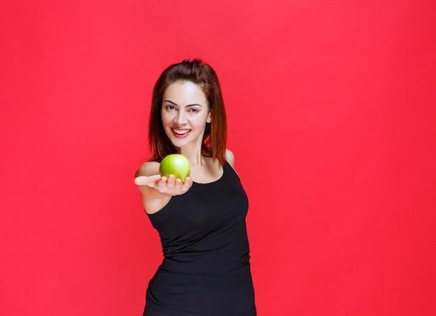 Giovane donna in canottiera nera che tiene mele verdi e le condivide con un amico