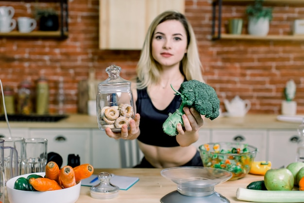 La giovane donna nello sport nero copre la scelta fra broccoli o alimenti industriali, bagel. concetto di cibo disintossicante pulito sano. concetto vegetariano, vegano, crudo. copia spazio.