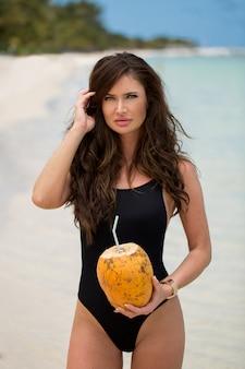 Giovane donna in costume da bagno nero con cocktail di cocco sulla spiaggia