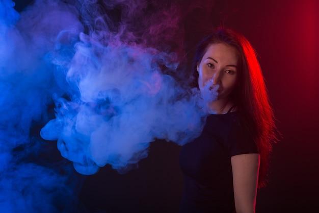 Giovane donna in maglietta nera che vaping in luce al neon rossa e blu.