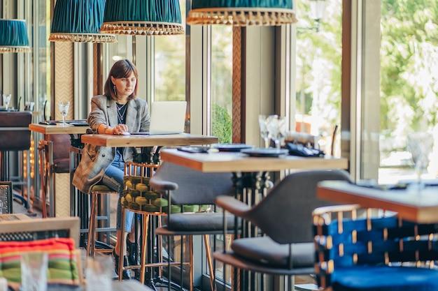 Giovane donna in giacca con laptop nella caffetteria vicino alla finestra. professioni è una blogger, freelance e scrittrice. libero professionista che lavora in una caffetteria. imparare in linea.